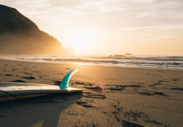 surf board on beach at sunset