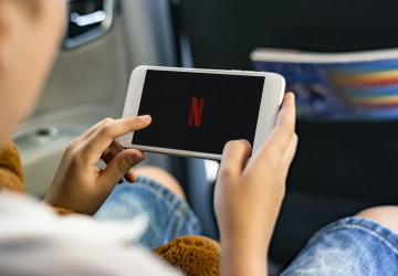 child in car watching netflix on phone