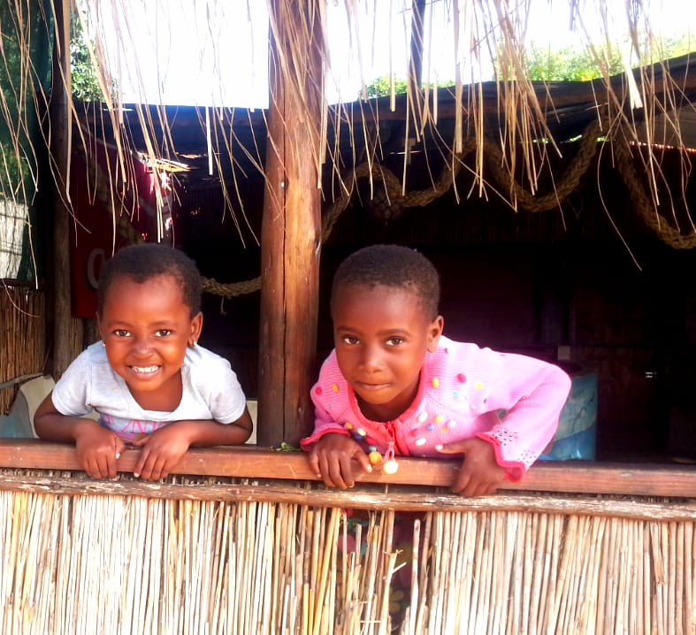 2 children from ponta malongane hanging over fence